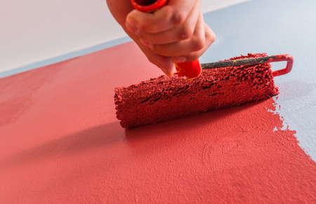 hombre rojo: Cierre de rodillo de pintura en la pared.