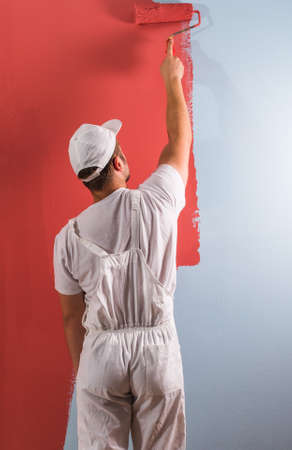 eastern european ethnicity: Young man painting wall with roller