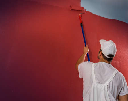 hombre pintando: Young man painting wall with roller