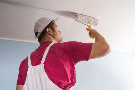 heights job: Young Painter In White Uniform Painting With Paint Roller
