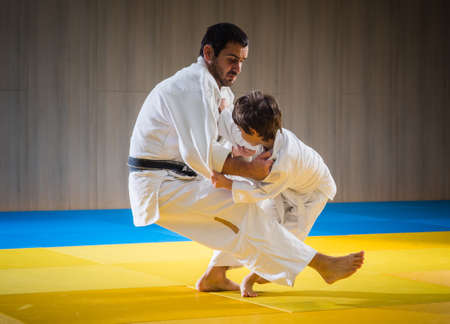 gi: Man and young boy are training judo throwing