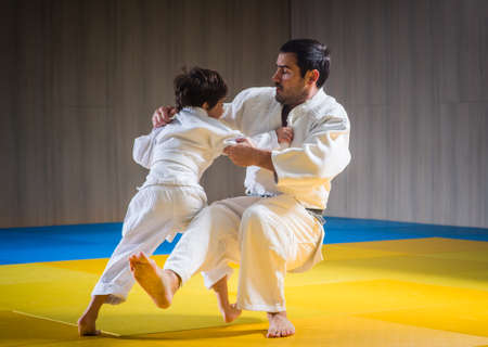Man and young boy are training judo throwing