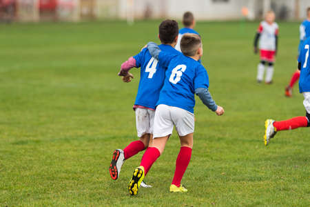 only boys: Young soccer boys huging during football match on the field
