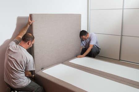 king size: Furniture maker sets bed in bedroom Stock Photo