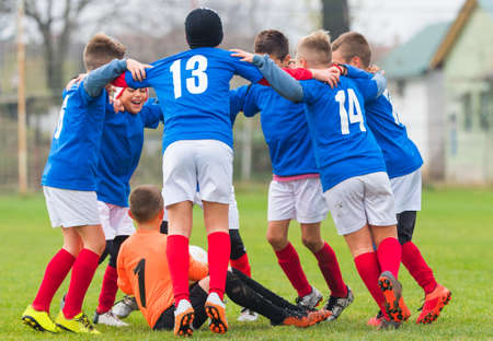 Jonge jongens in het voet bal team vieren