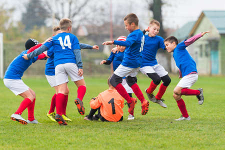child laughing: Young Boys In Football Team Celebrating Stock Photo