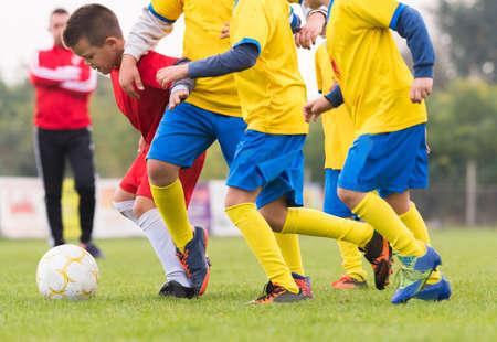kicking: boys kicking football on the sports field