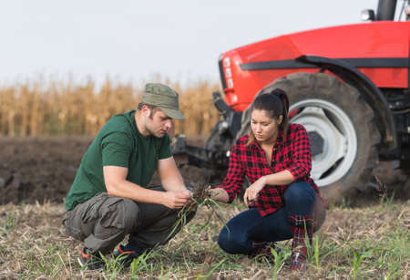 woman in field: Young farmers examing dirt while tractor is plowing field