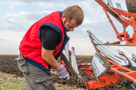 Young mechanic fixing plow on the tractor Stock Photo