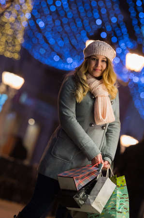 Young happy pretty woman walking at night with christmas decorations.