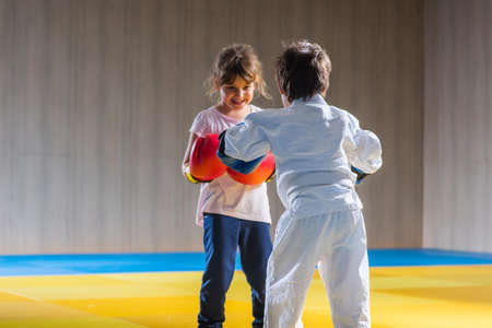 pinching: Young kids with boxing gloves training