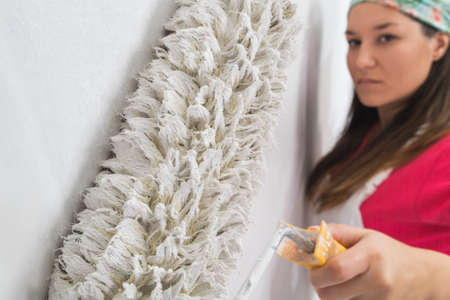 hair roller: Happy pretty young woman painting a wall
