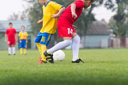 football socks: boys kicking football on the sports field
