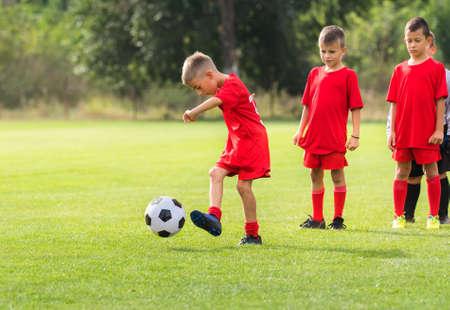 Boy kicking soccer ball at training on sports field