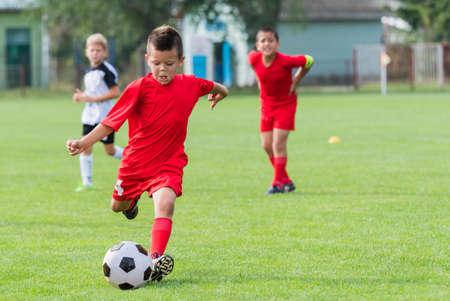 Jongen schopt voetbal bal op sportveld Stockfoto - 70836520