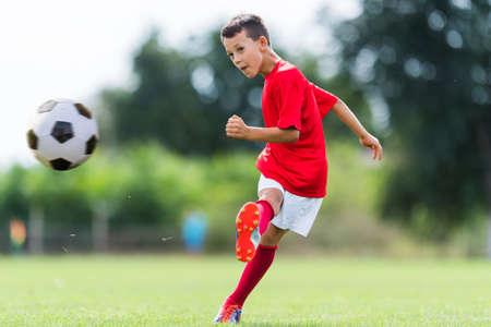 kicking: Boy kicking soccer ball on sports field Stock Photo