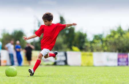 Jongen schopt voetbal bal op sportveld