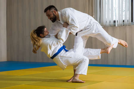 Young woman and man judo fighters in sport hall 스톡 콘텐츠