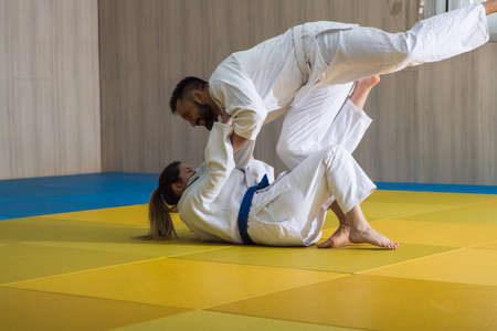 Young woman and man judo fighters in sport hall Stock Photo