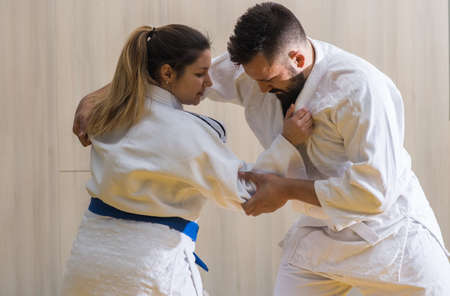 sport hall: Young woman and man judo fighters in sport hall Stock Photo