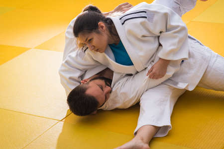 judo: Young woman and man judo fighters in sport hall Foto de archivo
