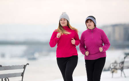 Mother and daughter wearing sportswear and running on snow during winter time Stock Photo