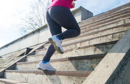 upstairs: Runner feet running upstairs closeup on sneakers - woman fitness sunrise jog workout welness concept