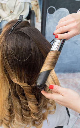 Professional hairdresser curling ombre hair with iron in beauty salon