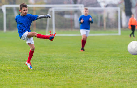 sports field: Boy kicking soccer ball on sports field Stock Photo
