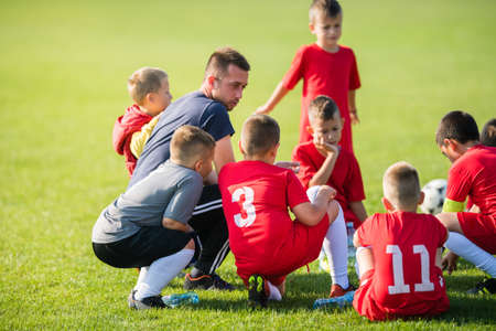 Kids soccer waiting in a out with coach