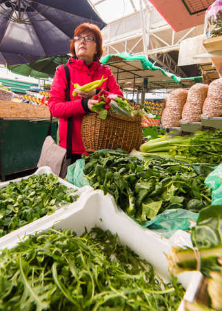 Middle age woman buying lettuce at market place Stock Photo