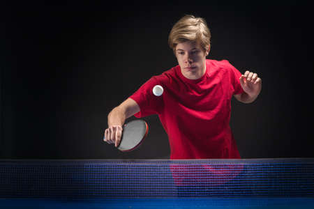 young man tennis player in play on black background photo