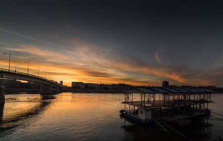 Beautiful warm sunset on the city panorama with buildings and colorful sky over the bridge and river Danube