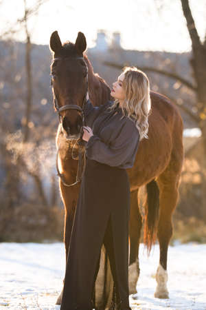 Young beautiful elegance modern woman posing with horse