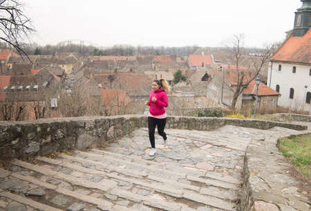 run down: Pretty girl wearing sportswear and running upstairs at city fortress