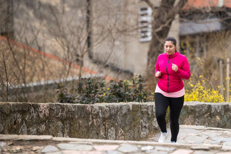 Pretty girl wearing sportswear and running upstairs at city fortress