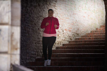 run down: Pretty girl wearing sportswear and running down stairs at city fortress Stock Photo