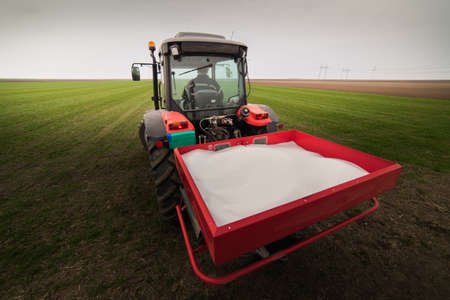 Tractor spreading artificial fertilizers  in field Foto de archivo