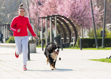 Young pretty girl running outdoor in the spring with her Bernese Mountain dog Stock Photo