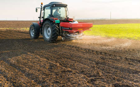 Tractor spreading artificial fertilizers  in field Archivio Fotografico