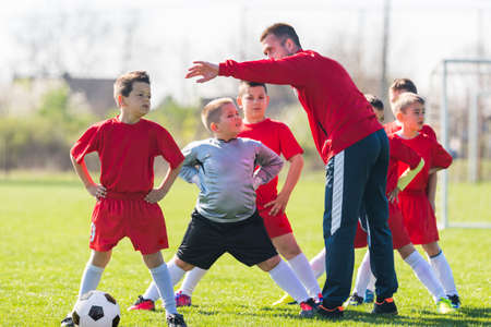 warm up: Kids soccer football - small children players exercising before match on soccer field Stock Photo