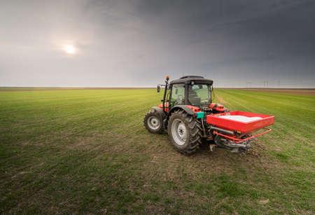 Tractor difundir fertilizantes artificiales en el campo Foto de archivo - 75485242