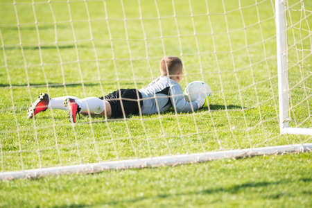 Kids soccer football - young goal keeper on the  match on soccer field