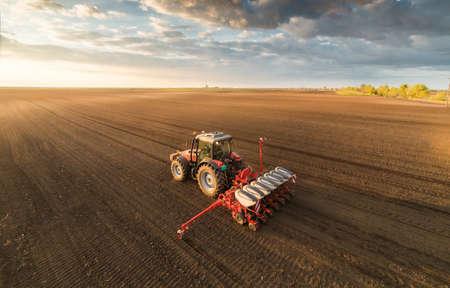 Landwirt mit Traktor Aussaat - Aussaat Getreide auf landwirtschaftlichen Feldern im Frühjahr Standard-Bild - 75584028