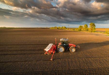 Landwirt mit Traktor Aussaat - Aussaat Getreide auf landwirtschaftlichen Feldern im Frühjahr Standard-Bild - 75584036
