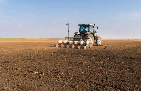 Farmer with tractor seeding - soy sowing crops at agricultural fields in spring