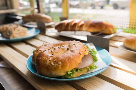 Fresh bun sandwich with ham, cheese, bacon, tomatoes, lettuce, cucumbers on light wooden table at window shops Stock Photo