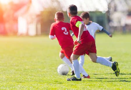 jugadores de futbol: Kids soccer football - young children players match on soccer field Foto de archivo