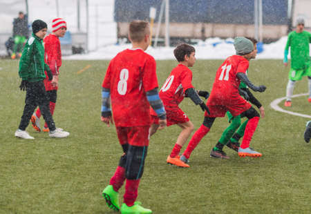 Young kids soccer football tournament - children players match on soccer field during the snow falling Stock Photo