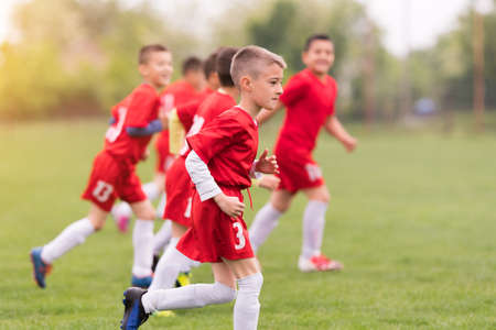 Kids soccer football - small children players exercising before match on soccer field Stock Photo